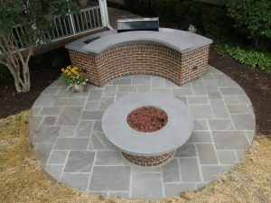 Round Outdoor Kitchen with Bent Gray Concrete Countertop