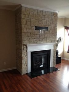small carved stacked stone fire place face