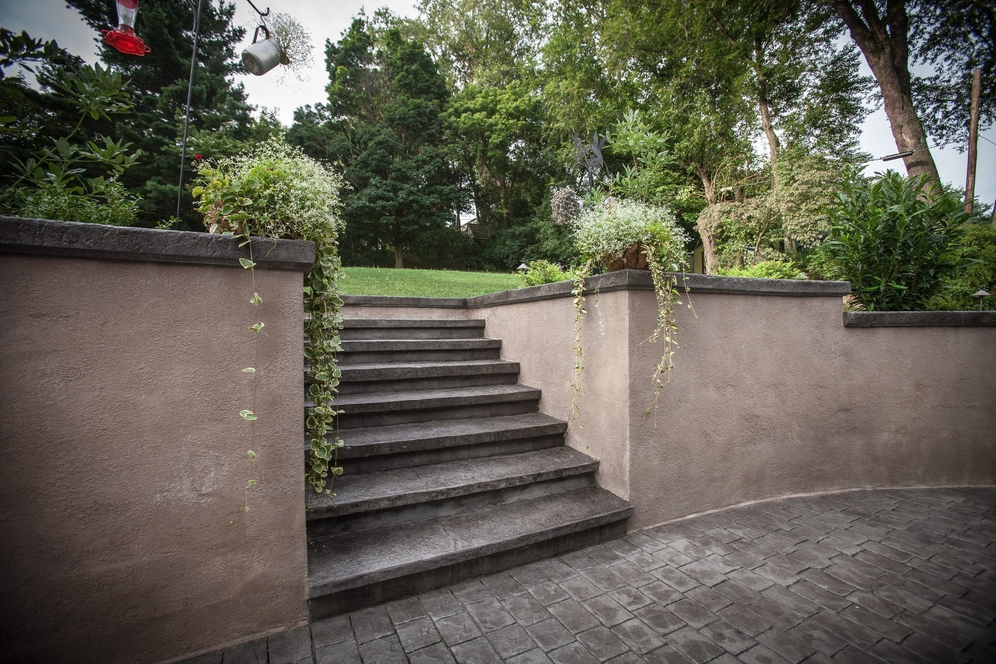 Backyard stamped concrete and wall spray into retreat for Stucco garden wall designs