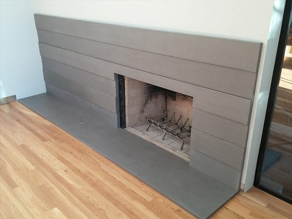Fireplaces don't always have to look old an. The thin gray modern concrete panels create wonderful modern look for this fire place surround.