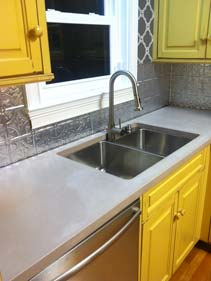 Light Gray Thin Concrete Counters with under sink Yellow Cabinets